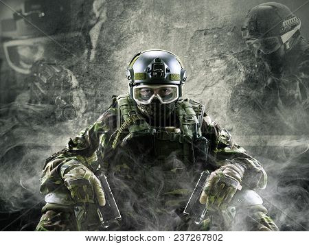 A Special Forces Soldier Sits On A Gray Background With A Smoke Effect. Holds A Gun In His Hands And