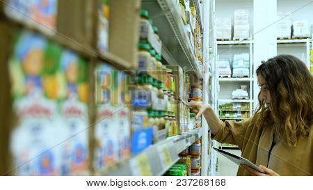 Young Woman With A Tablet Buys Baby Food In A Supermarket, The Girl Carefully Studies The Compositio