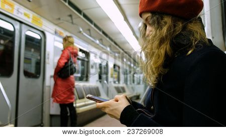 Woman Uses A Smartphone In The Subway, The Girl Uses The Phone In The Car.