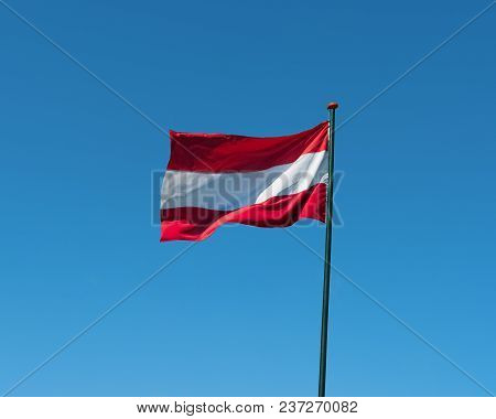 Flag Of Austria On Flagpole Waving In The Wind. Austrian National Official Flag On Blue Sky Backgrou