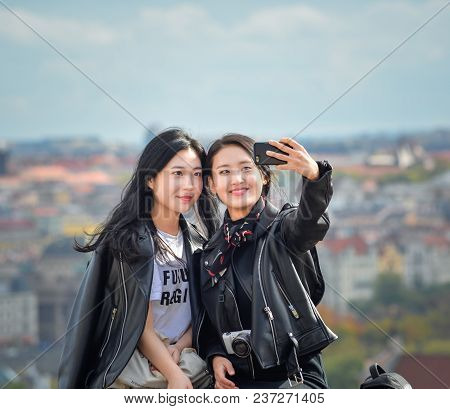 Prague, Czech Republic - October 10, 2017: Two Pretty Asian Girls Taking Selfie Selfie And Looks At
