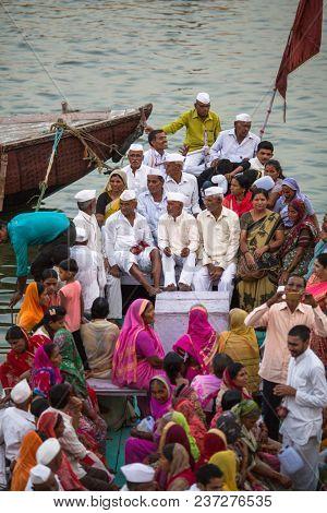 VARANASI, INDIA - MAR 29, 2018: Pilgrims expect ritual Agni Pooja (Sanskrit: Worship of Fire) on Dashashwamedh Ghat - main and oldest ghat of Varanasi located on the Ganges.