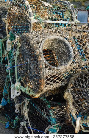 Lobster And Crab Pots Or Traps Stacked On A Harbour Wall Used For Catching Crustaceans