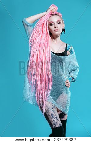 Sexy girl with pink dreadlocks posing in kombidress on a gray background. Beauty, fashion.