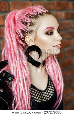 Sexy girl with pink dreadlocks posing by the brick wall. Beauty, fashion.