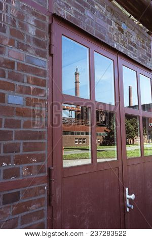 Window Reflection Of Chimneys And Coking Plant On The Grounds Of The Zeche Zollverein