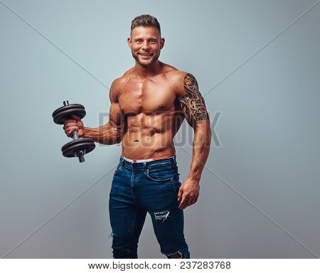 Smiling Handsome Shirtless Bodybuilder With Stylish Haircut And Beard, With Tattoo On His Arm, Posin