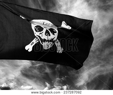 Black And White Jolly Roger (pirate Flag) Against Storm Clouds