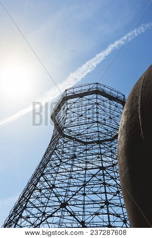 Old Industrial Cooling Tower With Sun On Blue Sky