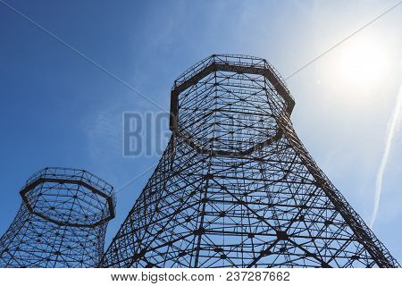 Two Old Industrial Cooling Towers With Sun On Blue Sky