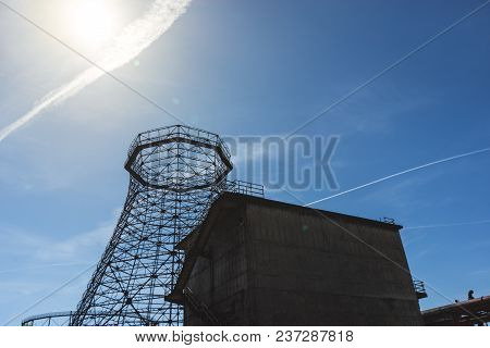 Old Industrial Cooling Tower Framed Of Industrial Building With Sun On Blue Sky
