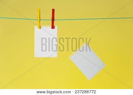 Done Notes Background. Notepad Blank Pages On Rope And Falling Over Yellow Background.