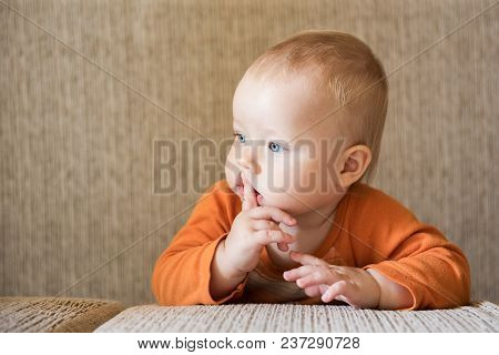 Pensive Attractive Baby Boy With Finger In Mouth