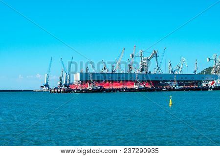 Shipyard And Cranes On Blue Sky And Sea Background. Industrial Scene