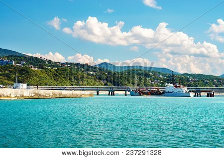 White Ship Stay Near A Pier On Background Of Southern Resort Town And Hills. Natural And Industrial