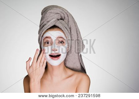 Beautiful Young Girl With A Towel On Her Head, After Showering, Applied A Useful Moisturizing Face M
