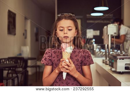 A Beauty Little Girl In A Fashionable Dress Holds Strawberry Ice Cream, Standing In An Ice Cream Par