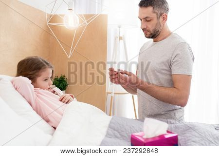 Loving Daddy. Fair-haired Sick Girl Lying In Bed And Her Daddy Holding A Thermometer
