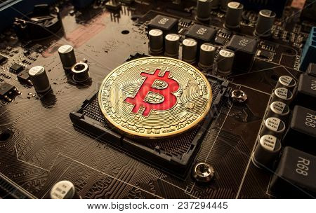 Gold Bit Coin BTC coins on the motherboard. Bitcoin is a worldwide cryptocurrency and digital payment system called the first decentralized digital currency.