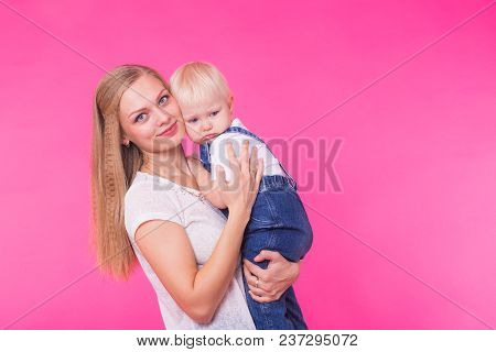 Happy Little Girl And Her Mother Having Fun Over Pink Background.