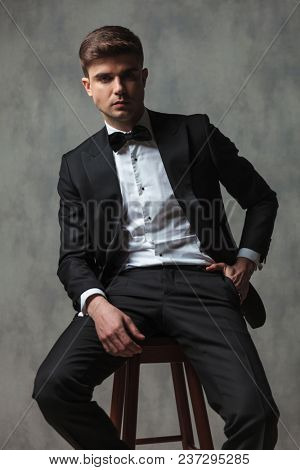 relaxed businessman dressed elegantly in a black tuxedo with a black bowtie sitting on a wooden chair with hand in pocket and leaning back on grey wall background
