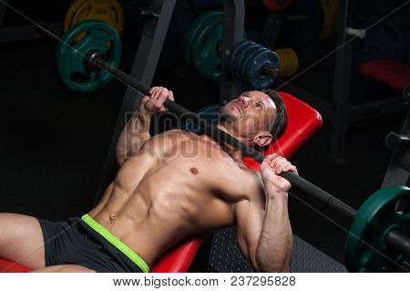 Sports Concept. Strong Young Man In A T-shirt And Shorts Doing Bench Press With Barbell In The Gym