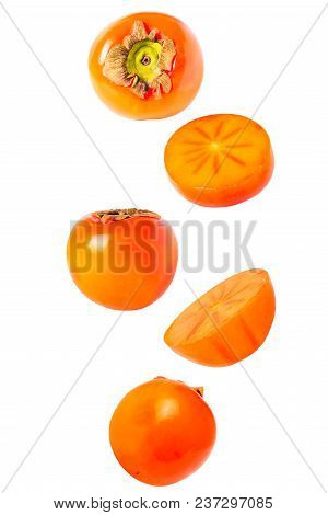 Isolated Falling Fruits. Falling Sweet Perssimon Fruits Isolated On White Background With Clipping P