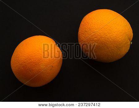 Two Bright Orange Oranges. Oranges On A Black Background. Two Oranges On A Black Background.