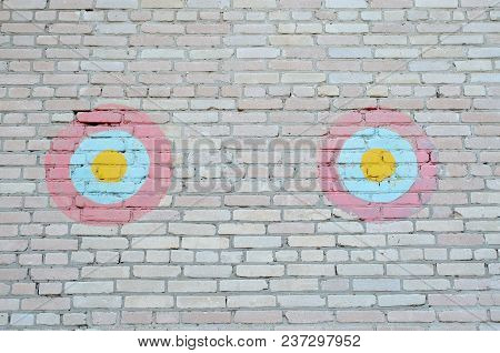 Two Decorative Red-blue-yellow Circles On A Brick Wall
