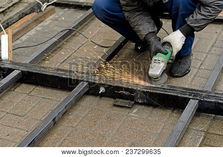 Worker In Gloves Cleans The Angle Grinder Metal Construction.copyspace Left