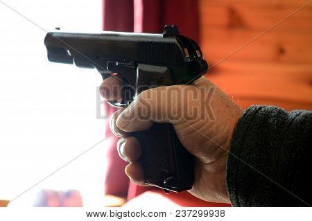 Closeup Of A Man Holding A Hand Gun Ready To Shoot.