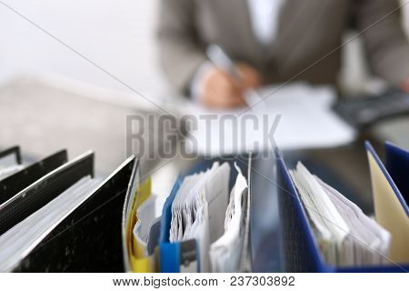Binders With Papers Are Waiting To Be Processed With Businesswoman Or Secretary Back In Blur.