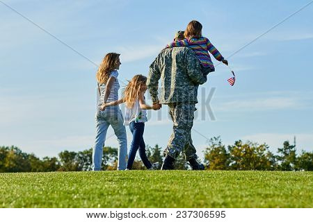 Back View Soldier And His Family Are Walking On The Grass. Patriotic Family With American Flags, Blu