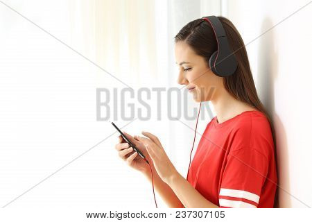 Side View Portrait Of A Relaxed Girl Listening To Music On White At Side