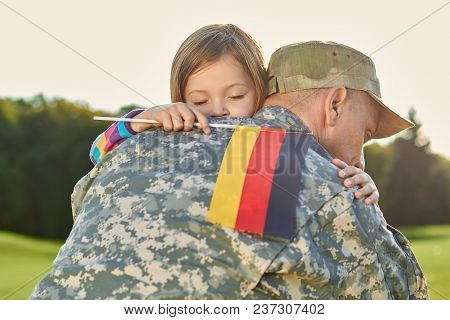 Happy Reunion Of German Family. Little Girl With Deutsch Flag Is Hugging Her Father.