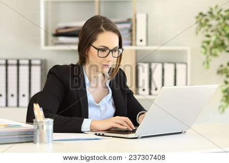 Single Office Worker Working Online With A Computer Sitting In A Desktop At Workplace