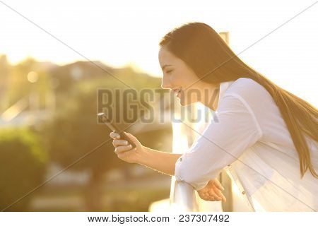 Side View Portrait Of A Woman Using A Smart Phone At Sunset In A House Balcony