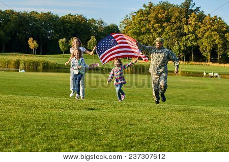 Patriotic Family Running With Huge American Flag. Soldier And His Family In Running With Big Usa Fla
