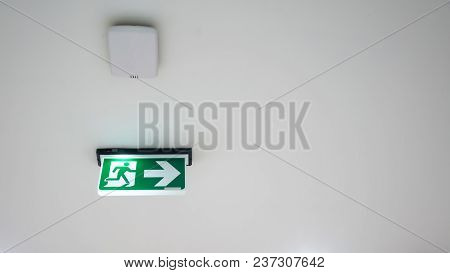 Green Emergency Exit Sign. Direction To The Escape Way On White Background.
