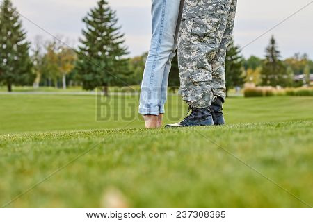 Woman Kissing Soldier Standing On Toes, Close Up. Girl Meet His Husband Came Back From The Army.