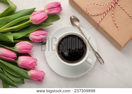 Pink Tulips, A Cup Of Coffee And A Gift On A Light Stone Background. Concept Of Spring.