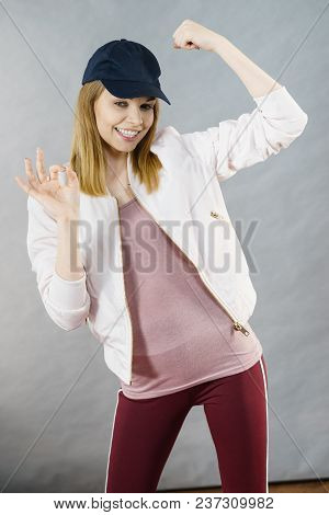 Young Sporty Woman Wearing Cap And Sportswear Showing Her Arm Muscles Enjoying Workout Results. Stud