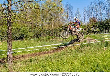 Biandronno, Italy - April 22, 2018: Motocross Rider In Jumping From The Trampoline Above The Road. O
