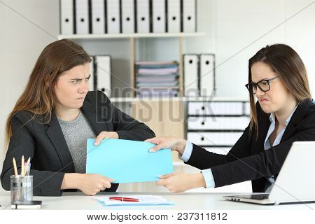 Two Angry Office Workers Fighting For A Project Sitting In A Desktop At Workplace