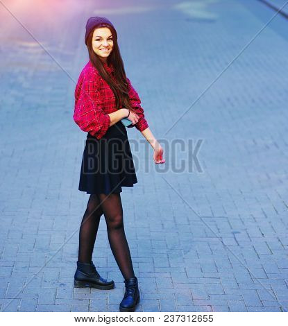 Cheerful Young Woman In Stylish Clothes Youth With A Smartphone In Hand, Smiling At The Camera. Happ