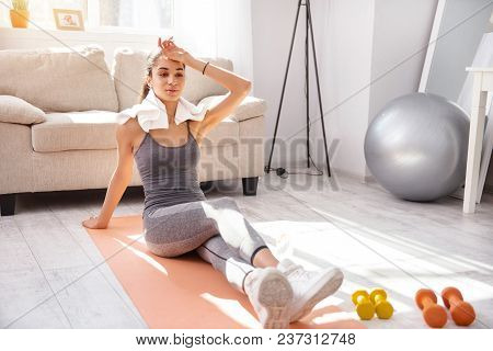 Well-deserved Break. Pleasant Young Woman Sitting On The Yoga Mat And Wiping Sweat Off Her Forehead