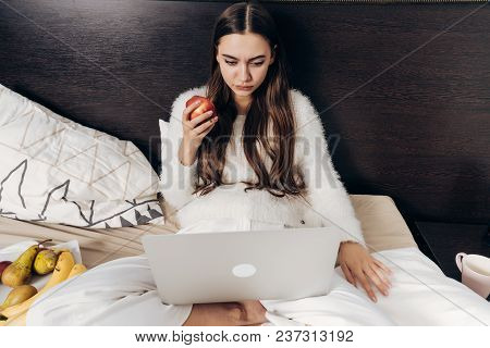 Serious Long-haired Girl In Pajamas Lies In Bed, Looks Interesting Episode On Laptop And Eats Apple