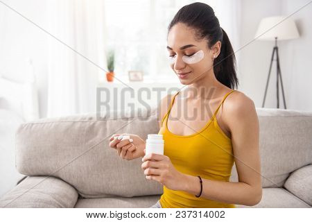 Necessary Medication. Charming Young Woman Sitting On The Sofa And Looking Inside The Bottle Of Vita