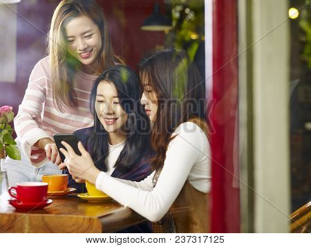 Three Happy Beautiful Young Asian Women Sitting At Table Chatting Talking Playing With Cellphone In