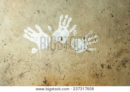 white imprints of human hands on wall concrete
